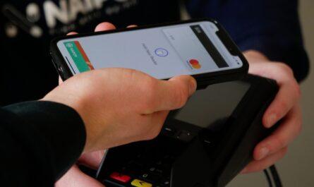 Muž využíván NFC platby při placení v obchodě.